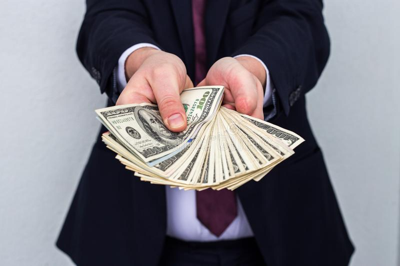 Business Man Displaying a Spread of Cash over a white vintage ba stock image