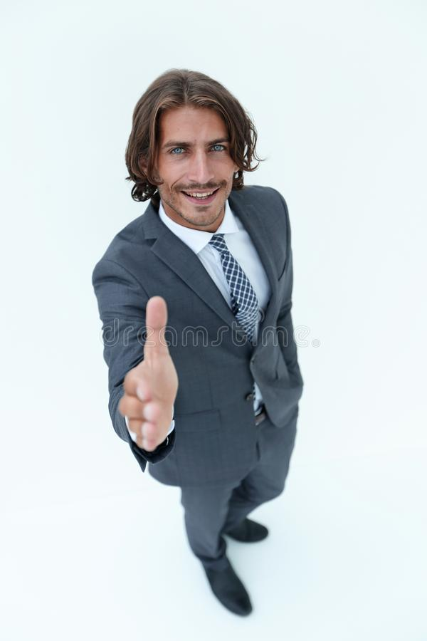 Business man extending hand to shake - focus om hand. Smiling middle aged businessman offering handshake on white background stock photo