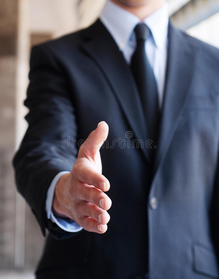 Business man extending for a handshake. Business man with an open hand ready to seal a deal stock images