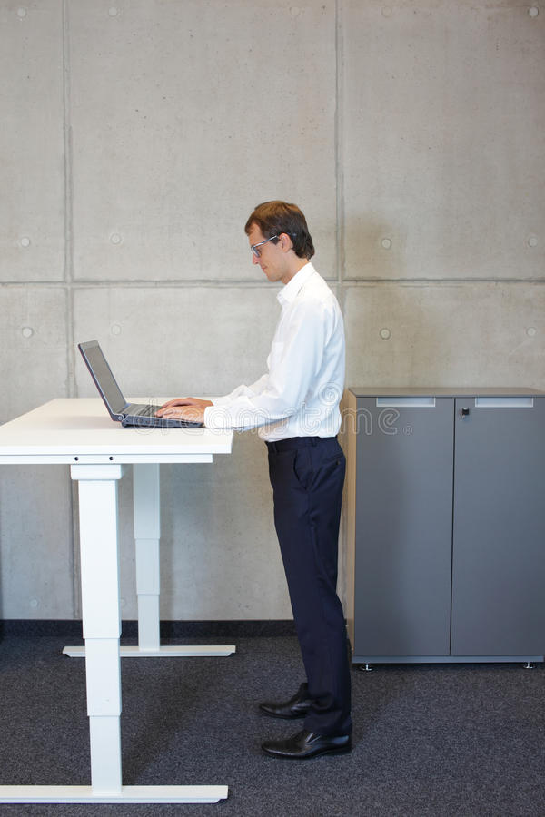 Business man with eyeglasses standing at height adjustment table. Business man with eyeglasses in white shirt standing at electrically controlled height stock image