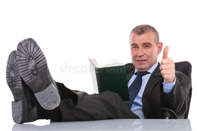 Business man with feet on desk holds a book and shows thumb up. Business man sitting with his legs on the desk and holding a book while showing the thumb up royalty free stock photos