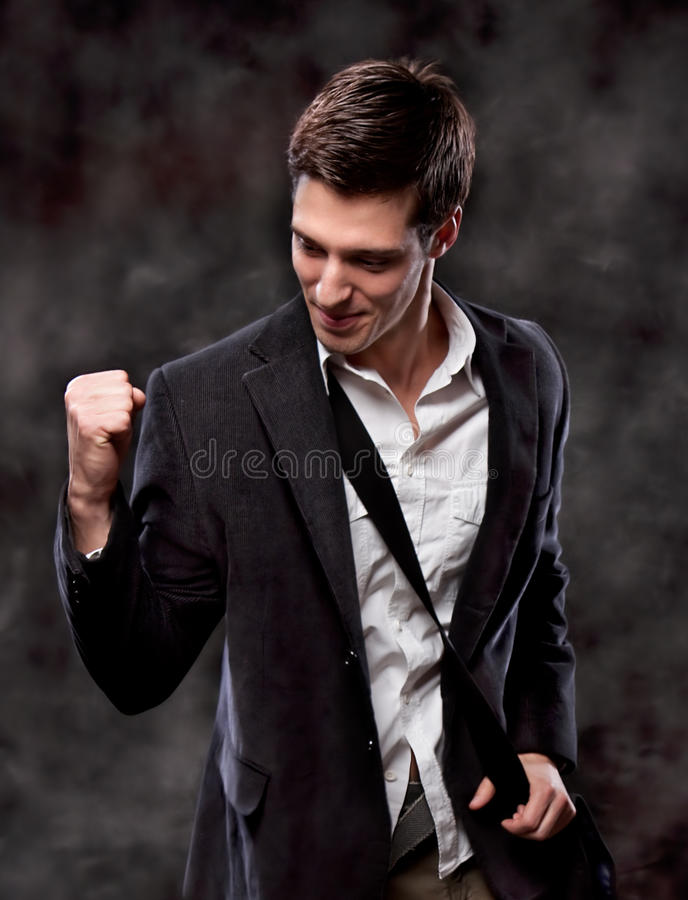 Business man with fists clenched in victory. Champion business man standing with fists clenched in victory. Studio shot stock image