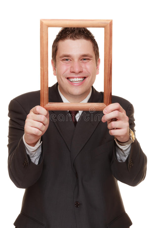 Business man framing his face with wood frame. Happy funny business man guy framing his face with wooden empty picture frame isolated on white background stock photos