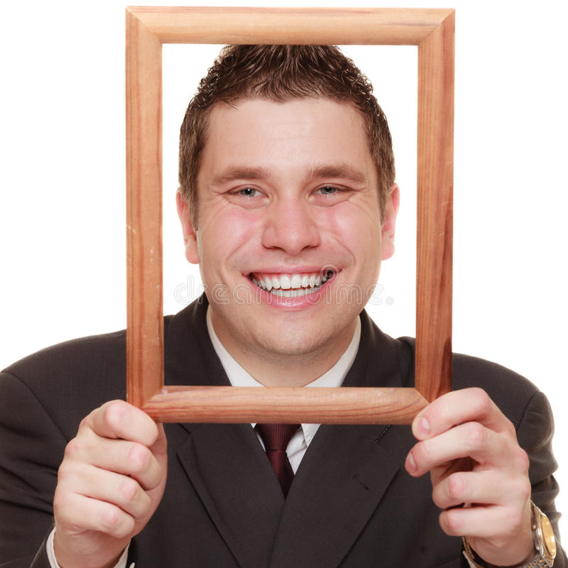 Business man framing his face with wood frame. Happy funny business man guy framing his face with wooden empty picture frame isolated on white background royalty free stock photography