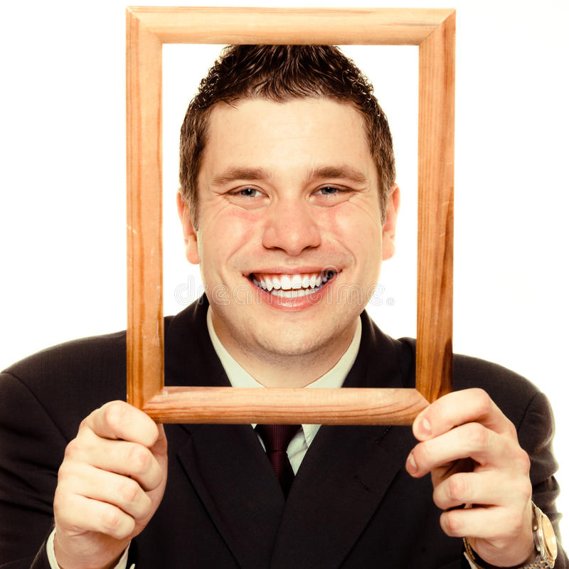 Business man framing his face with wood frame. Happy funny business man guy framing his face with wooden empty picture frame isolated on white background royalty free stock image