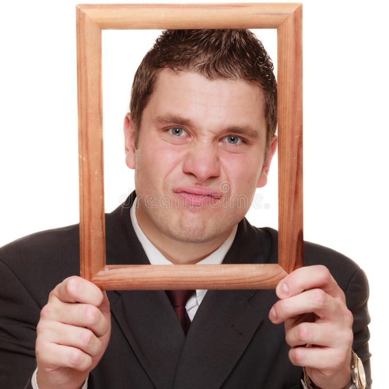 Business man framing his face with wood frame. Nerdy funny business man guy framing his face with wooden empty picture frame isolated on white background royalty free stock images