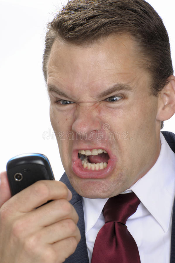 Business man furious with phone. Angry business man yells into cell phone royalty free stock images
