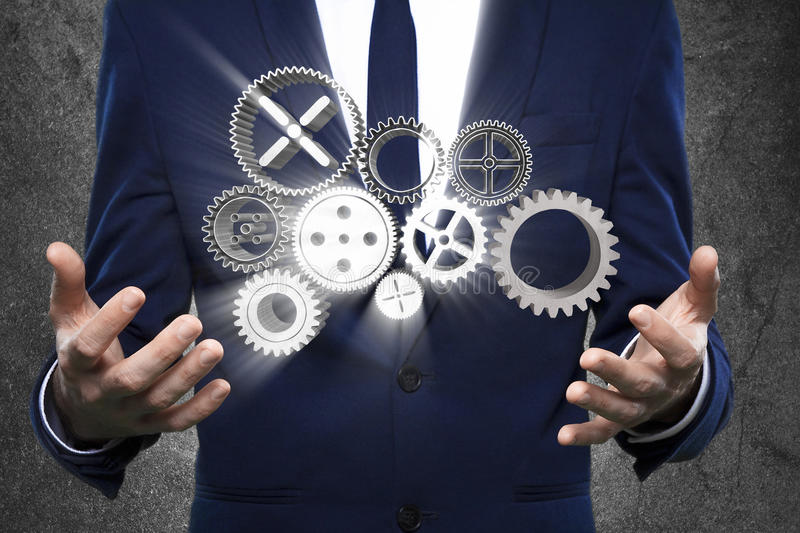 Business man with gears in hands stock photo