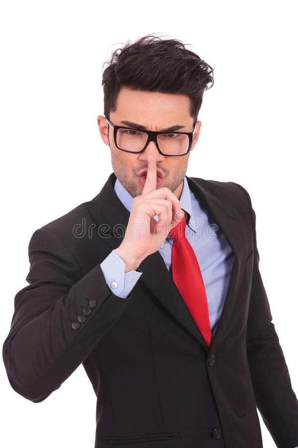 Business man gesturing shut up. Young business man showing the shut up sign with his finger against his mouth on a white wallpaper stock photography