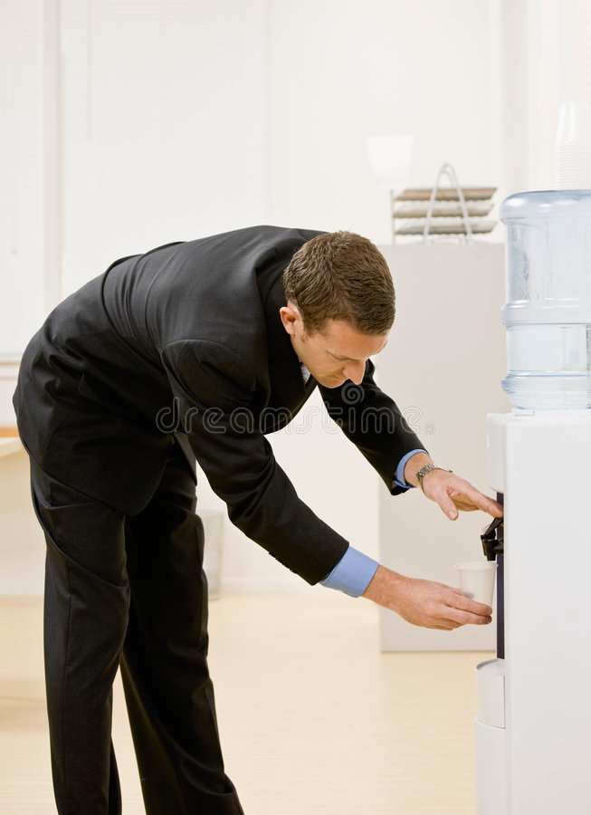 Business man gets water from water cooler stock image