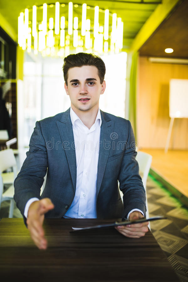 Business man give friendly handshake on camera in office stock photography