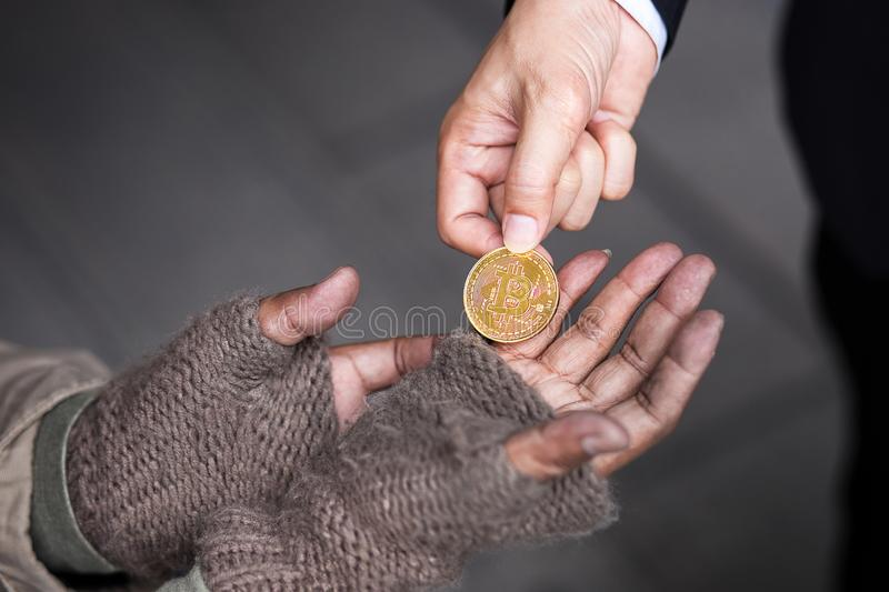 Business man give his gold bitcoin to homeless man. Business man give, donate, his gold bitcoin to homeless man in downtown of business zone stock photos