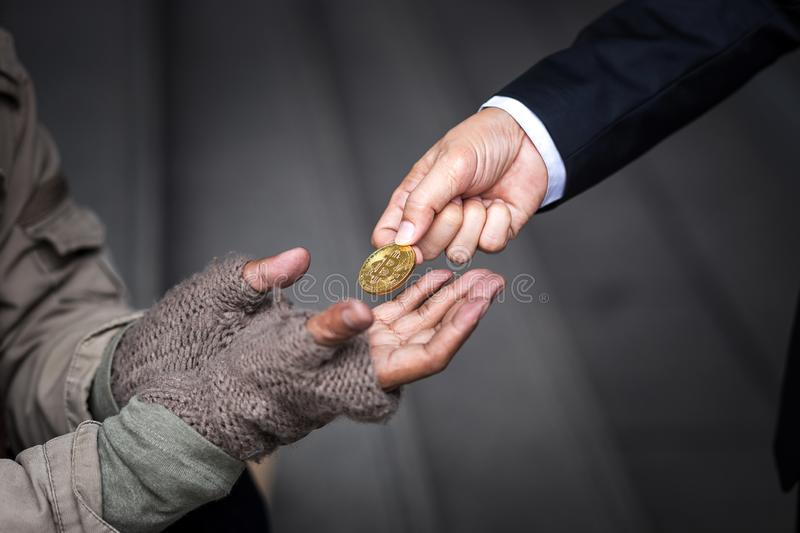 Business man give his gold bitcoin to homeless man. Business man give, donate, his gold bitcoin to homeless man in downtown of business zone stock photo