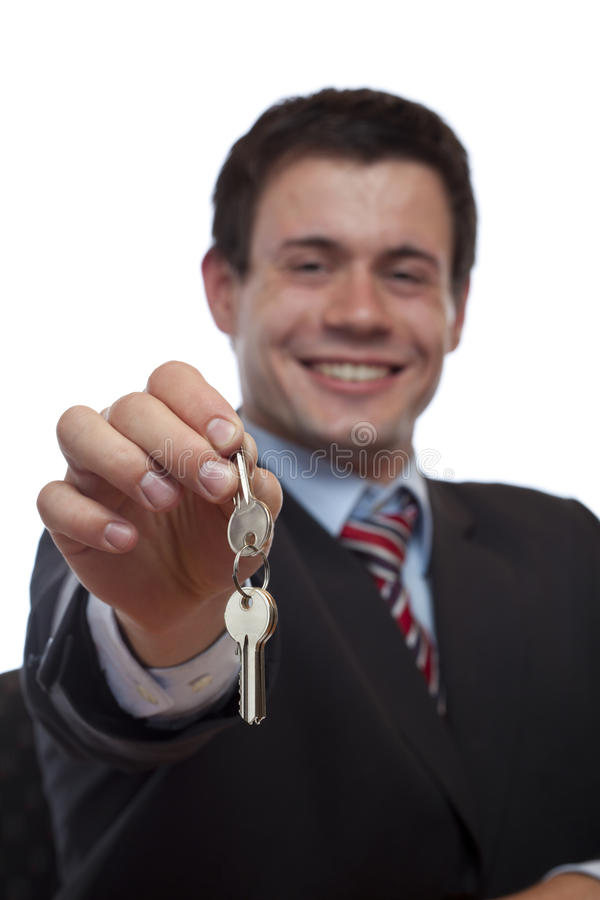 Business man gives over house key. Isolated on white background stock images