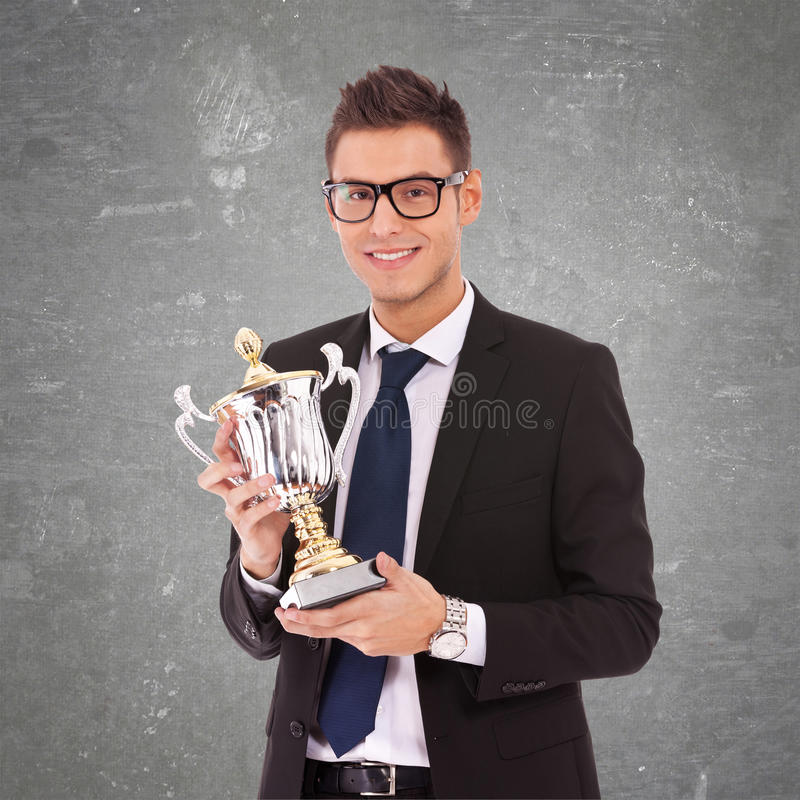 Business man with glasses holding a big trophy. Young business man with glasses holding a big trophy on gray background stock image