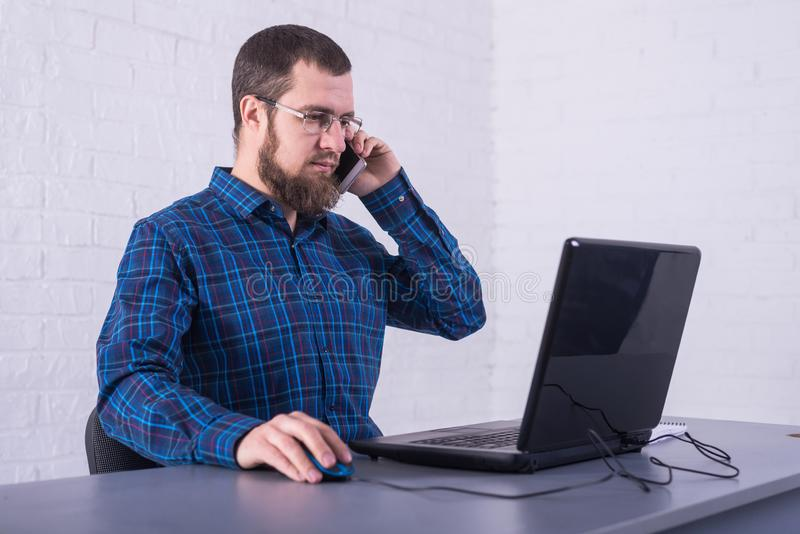 Business man in glasses works behind laptop and discussing on a cell phone space royalty free stock image