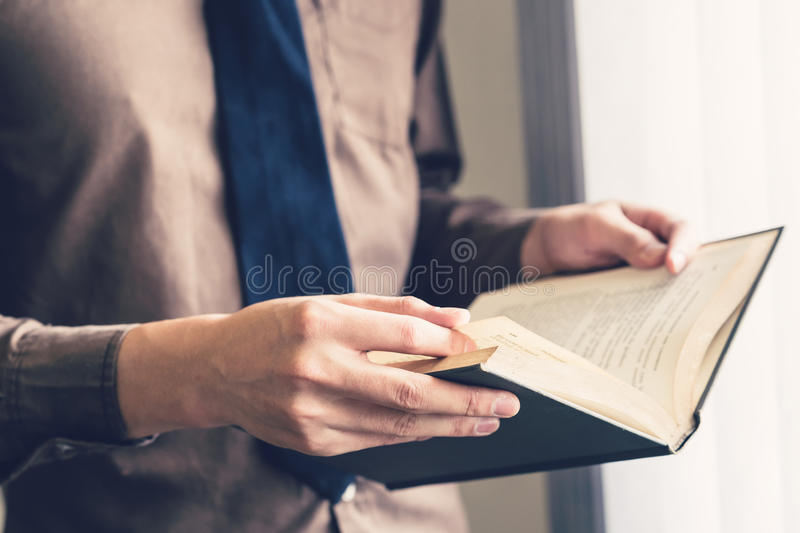 Business man hand holding book and reading at window royalty free stock photos
