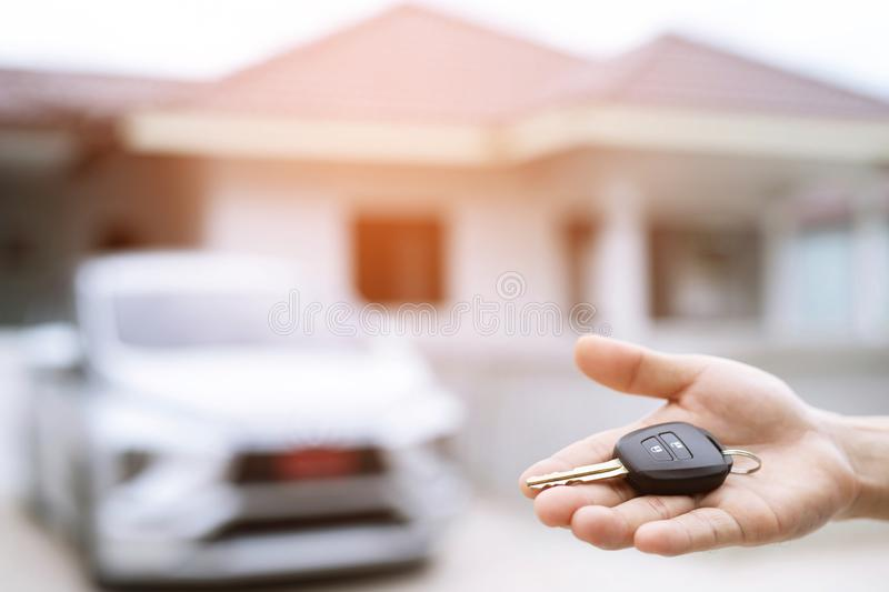 Business man hand holding car keys front with new car on background. parking in front of the house. transportation concept. stock images
