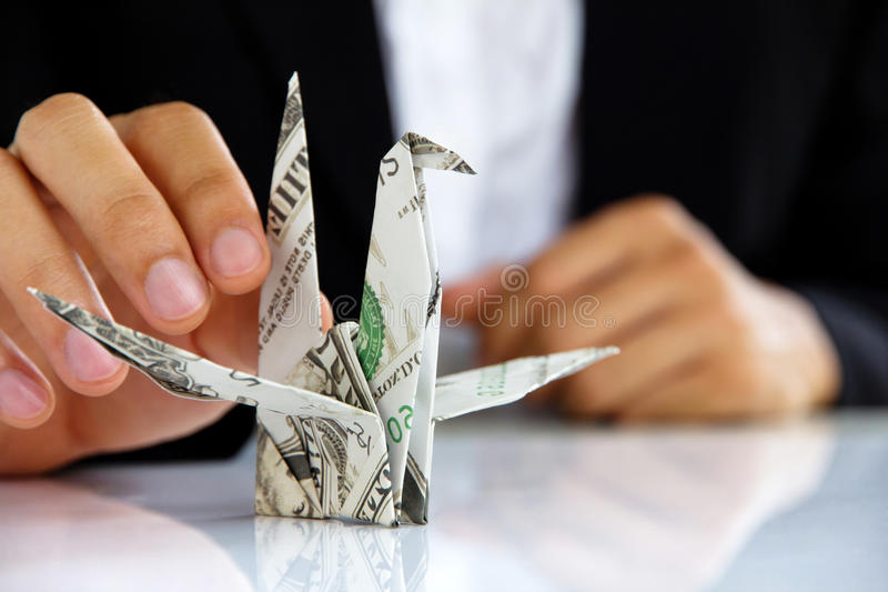 Business man hand holding origami paper cranes. Money concept stock photo