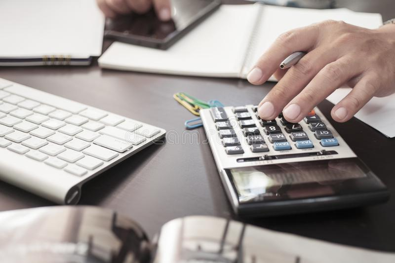 Business man hand holding pen using calculator and documents on office desk with laptop and smart phone ,office, business concept, royalty free stock photos
