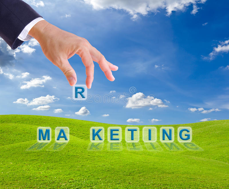 Business man hand and marketing word buttons. On green grass meadow stock image
