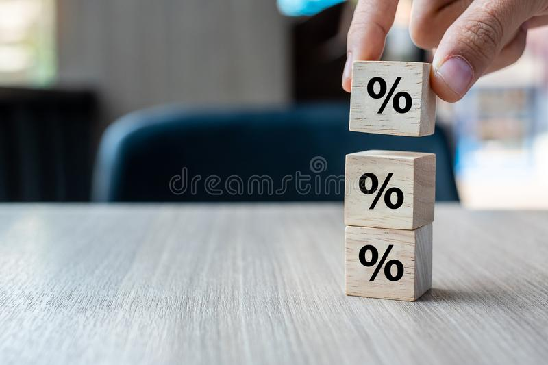 Business man Hand putting wood cube block with percentage symbol icon. Interest rate,  financial, ranking and mortgage rates. Concept royalty free stock image