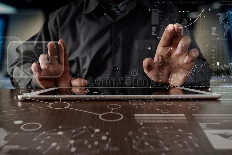 business man hand working on digital tablet computer with digital layer business strategy and social media diagram on wooden desk stock images