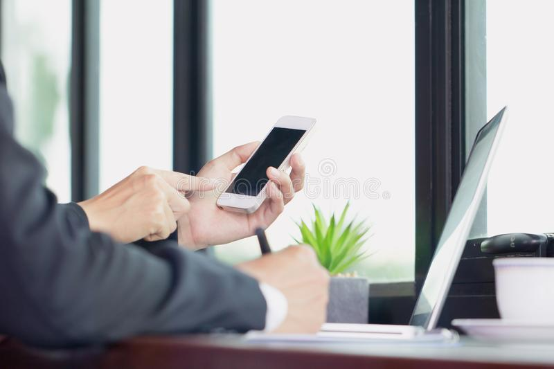 Business man hand working on smart phone and laptop computer stock photography