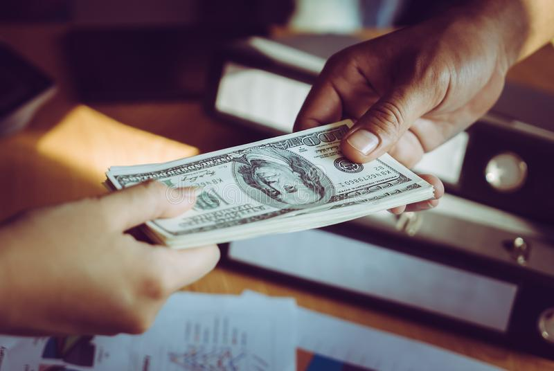 Business man handing money over a business dealing royalty free stock photography