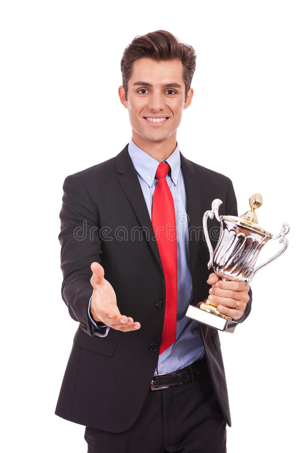 Business man handing a trophy and handshaking. Business man handing a trophy and is ready to handshake with the champion royalty free stock photos