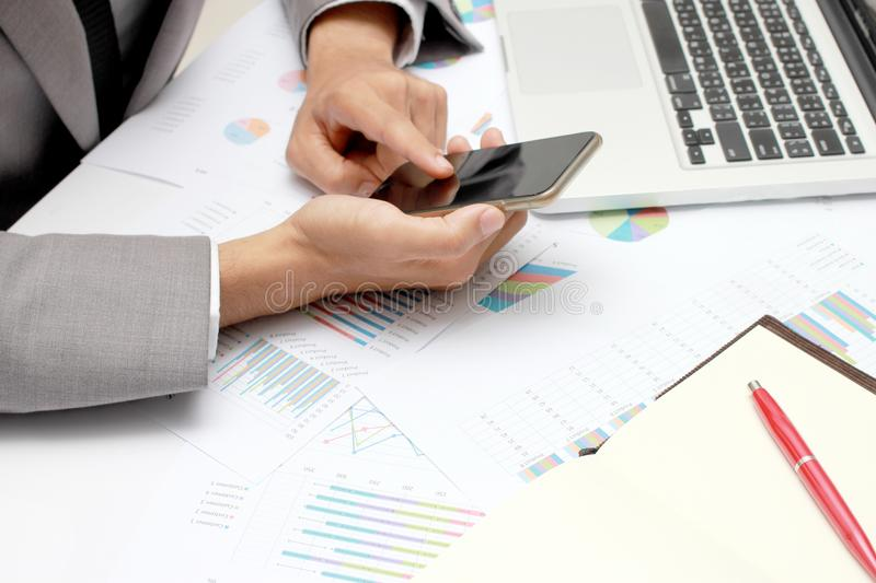 Business man hands busy using cell phone, laptop, pen and notebook at office desk. Analysis the charts and graphs showing the resu. Lts of their successful stock images