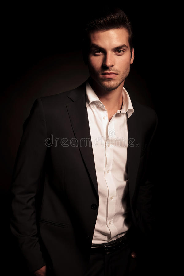 Business man with hands in his pockets on dark background royalty free stock photography