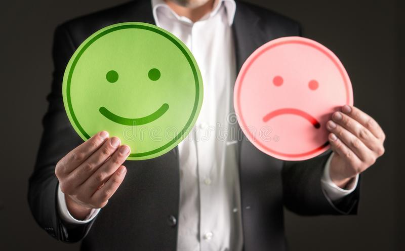 Business man with happy smiling and sad unhappy faces. Business man with happy smiling and sad unhappy cardboard paper smiley face emoticon. Rating and giving royalty free stock photos