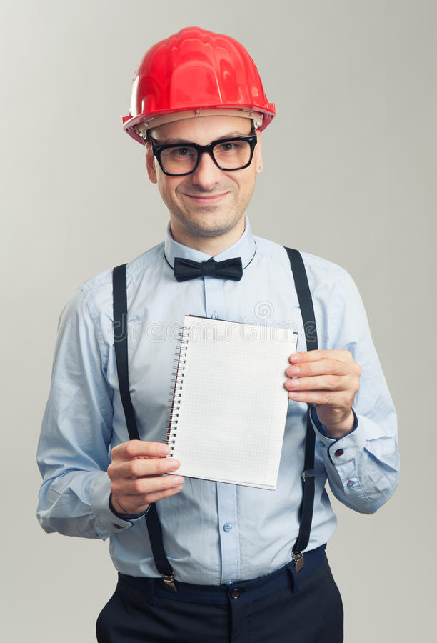 Business man in a helmet shows the blank sheet of notepad royalty free stock image