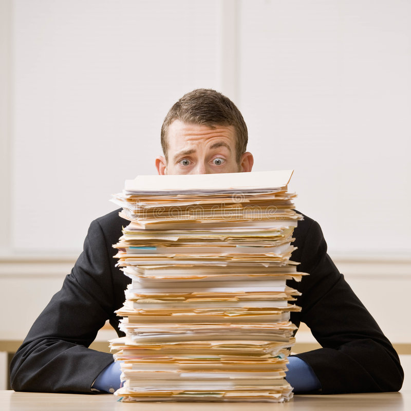Business man hiding behind tall stack of folders. Overworked, frustrated businessman looking at pile of file folders royalty free stock image