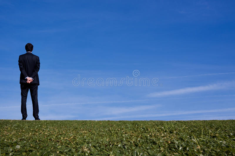 Business man on a hillside. Tall business man outdoors looking off into the distance royalty free stock photo