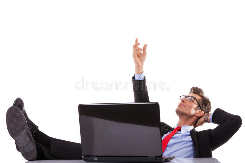 Business man at his desk with laptop, reaching out stock photography