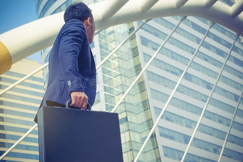 Business man holding a briefcase walking up the stairs in the routine of working with determination and confidence. stock photography