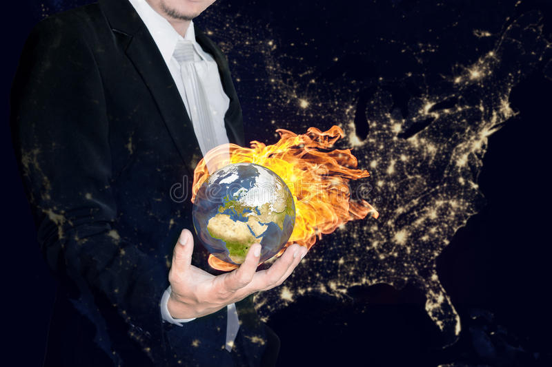 Business man holding the burning global earth in his hands royalty free stock image