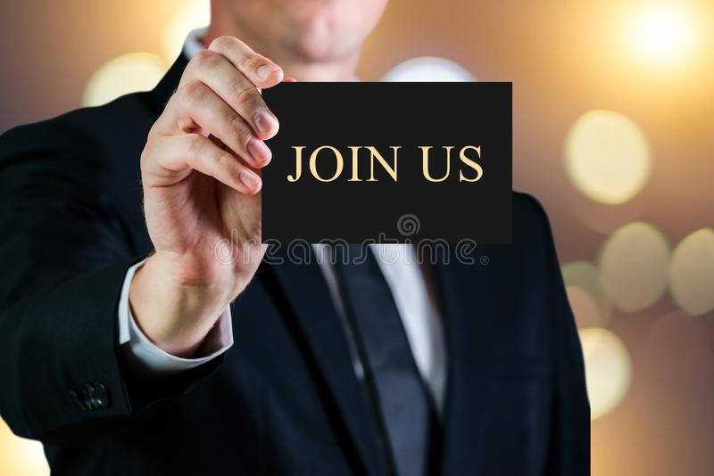 Business man holding a card on a luxury background. Join us message text. Hire or career concept. Business man holding a card on a luxury background. Join us stock photo