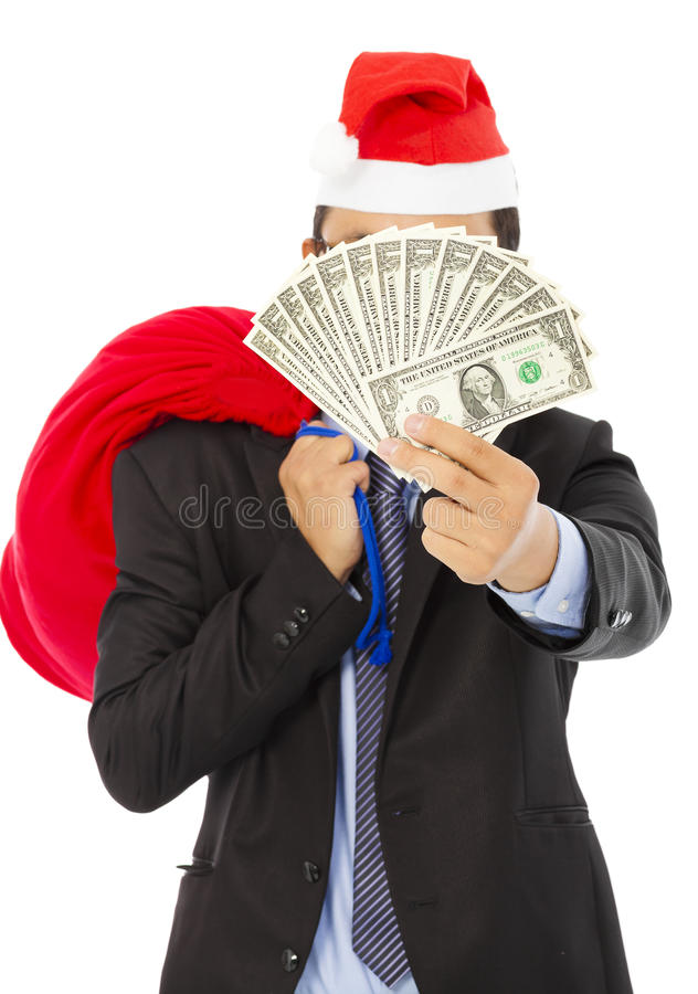 Business man holding a christmas gift bag and money. Over white background royalty free stock photography