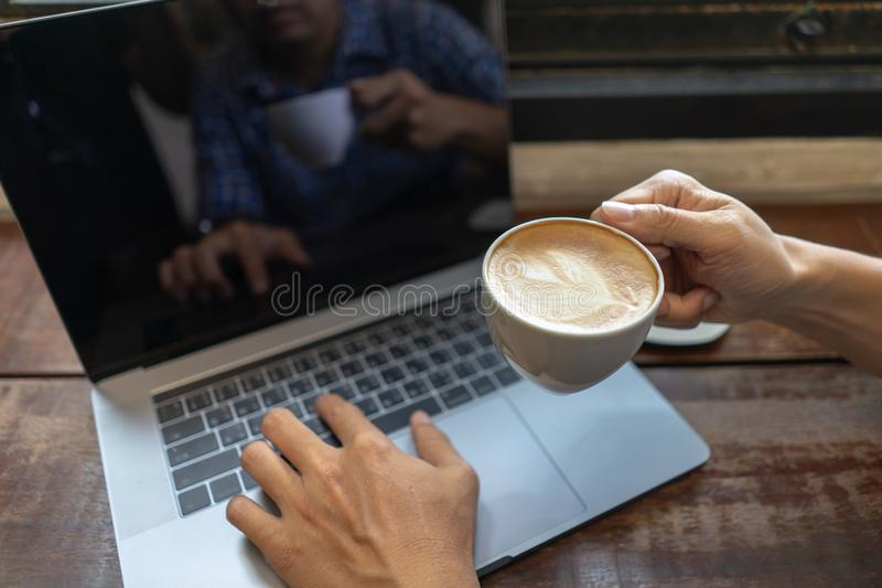 Business man holding coffee cup and typing on laptop computer keyboard on wooden table. Close up male hands with notebook pc royalty free stock photo