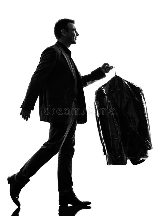 Business man holding dry clean clothes silhouette. One caucasian business man holding dry clean clothes in silhouette on white background stock photos