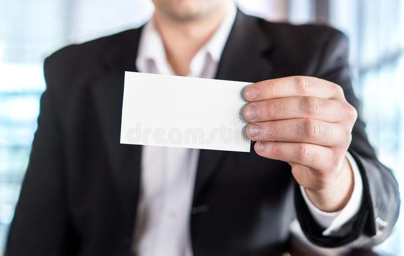 Business man holding empty white business card. stock photo
