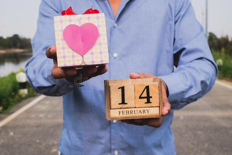 Business man holding 14 February wooden calendar and heart gift box. Valentine day concept.  royalty free stock photography