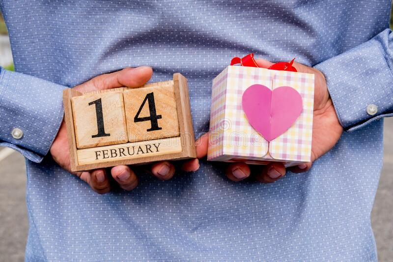 Business man holding 14 February wooden calendar and heart gift box. Valentine day concept.  royalty free stock images