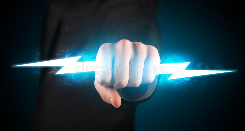 business man holding glowing lightning bolt in his hands stock photo