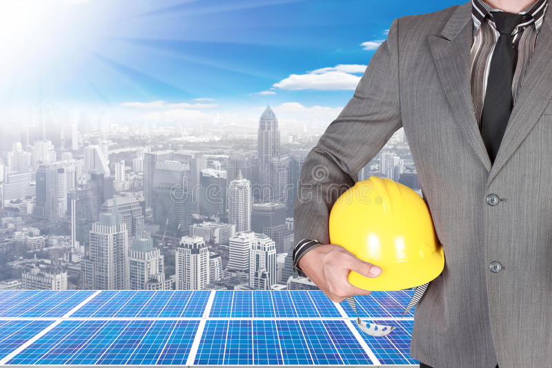 Business man holding helmet and solar energy panels on high building against beautiful sky with in concept ecology and real estate royalty free stock photography