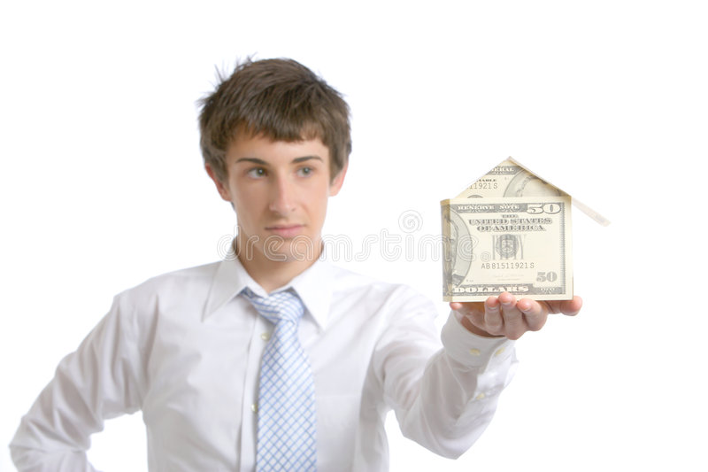 Business man holding a house made of money royalty free stock image
