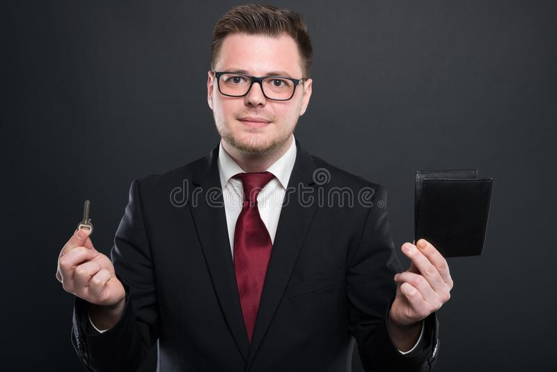 Business man holding key and black wallet stock photography